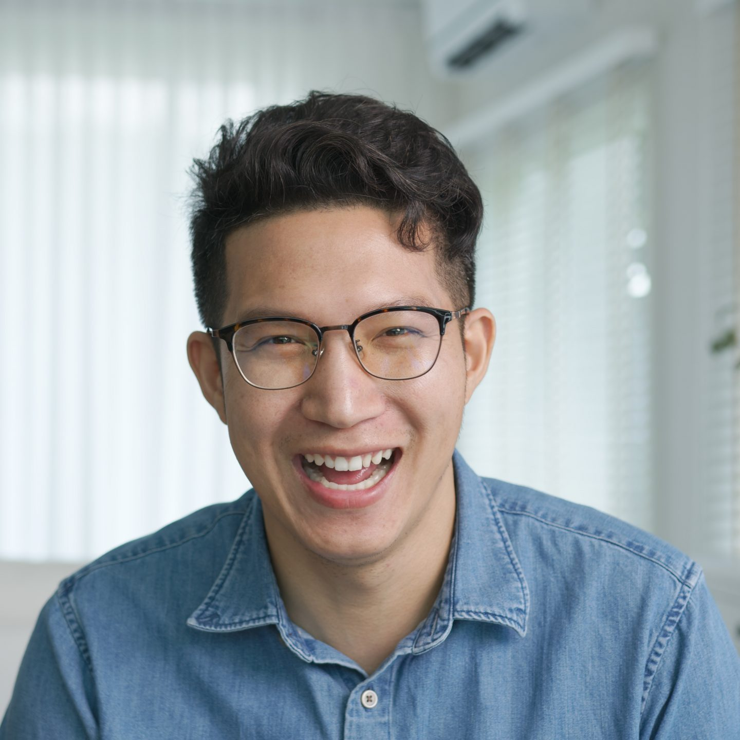 Portrait or headshot of young adult asian handsome man or model wearing eye glasses with cool hair big smiling confident and looking to camera with feeling happy and positive in living room at home.
